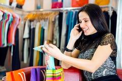 女孩谈话通过电话在商店 库存照片