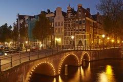 Амстердам, Нидерланды - дома на канале в голубом часе Стоковые Фото