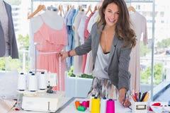 在时装模特的年轻时装设计师测量的礼服 库存图片