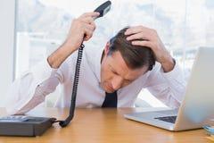 拿着电话的懊恼商人 免版税库存照片