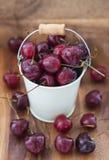 在一个白色桶的新鲜的湿樱桃在木背景 库存照片
