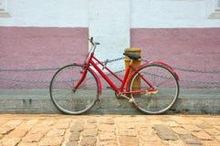 在古老街道上的老红色自行车 免版税库存图片