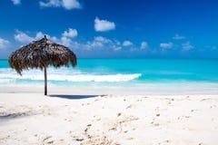 在一个完善的白色海滩的沙滩伞在海前面 免版税库存照片