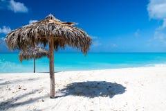 在一个完善的白色海滩的沙滩伞在海前面 库存照片