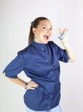 有哮喘吸入器的逗人喜爱的护士 免版税库存照片