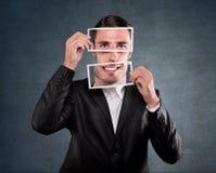 举行在他的面孔的商人微笑 免版税库存图片