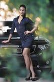 站立在花梢汽车旁边的时装模特儿,被弄脏的绿色起泡背景 免版税库存照片