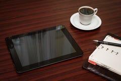 空的片剂和一杯咖啡在办公室 图库摄影