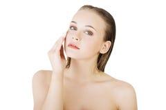 由化装棉的愉快的少妇清洁皮肤 免版税库存图片