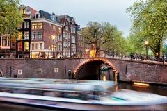 Путешествие моста и шлюпки канала в Амстердаме на вечере Стоковые Изображения RF