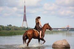 美丽的十几岁的女孩骑乘马在河 库存照片