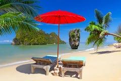 与遮阳伞和轻便折叠躺椅的热带海滩风景 库存照片