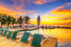 在热带游泳池的日落 库存照片