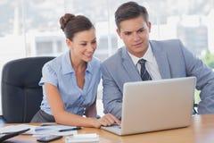 在膝上型计算机和微笑的商人 免版税库存图片