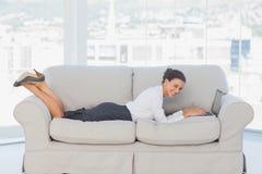 说谎在有膝上型计算机的长沙发的女商人 图库摄影