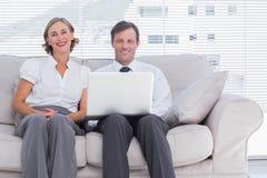 两个同事坐长沙发使用膝上型计算机在明亮的办公室 免版税图库摄影