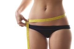 有磁带的妇女测量的腰部在白色背景 免版税库存图片