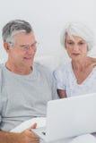 使用膝上型计算机的成熟夫妇 免版税图库摄影