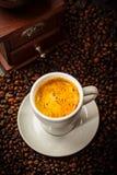 在咖啡豆的浓咖啡杯子 免版税库存图片