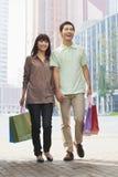 年轻夫妇走与购物袋的在手上,北京,中国 免版税库存照片