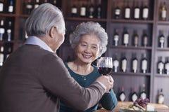 敬酒和开心的资深夫妇饮用的酒,在女性的焦点 免版税库存图片