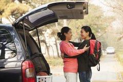 拥抱在学院校园里的汽车后的母亲和女儿 免版税库存图片