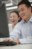 研究他们的计算机的愉快的商人在办公室 免版税库存照片