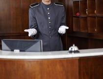 在旅馆招待会柜台后的看门人 免版税图库摄影
