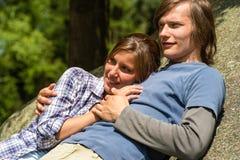 享受阳光的白种人夫妇说谎在岩石 免版税库存图片