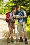 检查地图的年轻远足者夫妇 免版税库存图片
