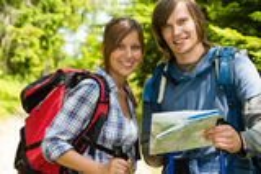 检查地图的迁徙的夫妇画象  免版税库存照片