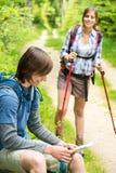 男性远足者观看的地图等待的女孩 库存照片