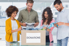 Счастливая команда волонтеров принимая вне одевает от коробки пожертвования Стоковые Изображения RF