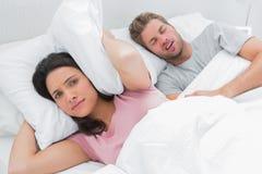 有枕头的生气妇女覆盖物耳朵在打鼾的丈夫旁边 免版税图库摄影