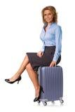 妇女坐手提箱 免版税库存照片