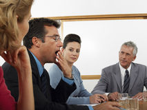 打呵欠在会议期间的商人在会议室 免版税库存图片