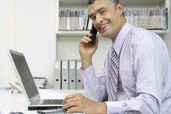 与膝上型计算机的商人使用在书桌的手机 图库摄影