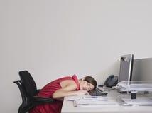 女性办公室工作者睡着在书桌 免版税库存照片