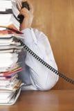 Άτομο που μιλά στο τηλέφωνο πίσω από έναν σωρό των φακέλλων Στοκ φωτογραφία με δικαίωμα ελεύθερης χρήσης