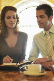 Бизнесмены подготавливая план-график на кафе Стоковое Фото