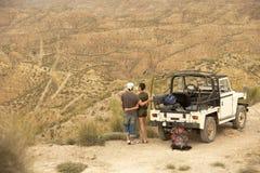 夫妇乘看从峭壁的汽车沙漠 免版税图库摄影