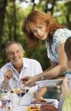 妇女在家庭的服务食物在表上 库存照片