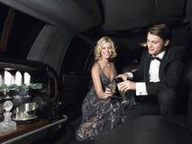 享受在大型高级轿车的夫妇香宾 图库摄影