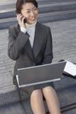 使用膝上型计算机和手机的女实业家户外 免版税库存图片