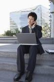 使用户外膝上型计算机和手机的商人 库存图片