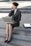 使用膝上型计算机和手机的女实业家户外 免版税库存照片