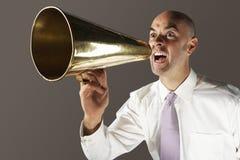 呼喊通过扩音机的秃头商人 库存照片