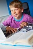 学习在卧室的男孩使用膝上型计算机 免版税库存照片