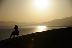 人在日出的骑乘马 免版税图库摄影