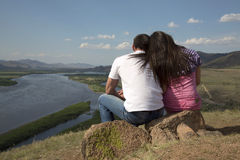 Пары сидя на утесе в горах Стоковая Фотография RF